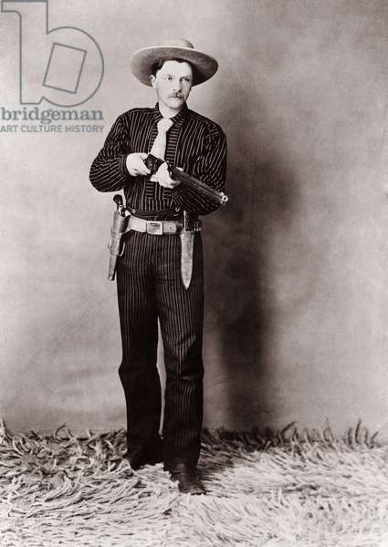 Bill Bennett, Wild West detective, armed with a rifle, revolver and knife. c. 1900
