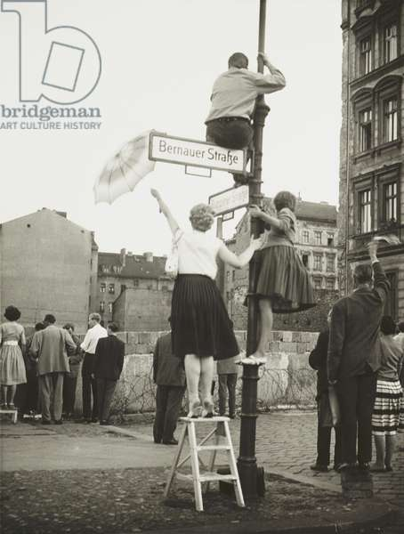 West Berliners in the French sector waved to friends and relatives in East Berlin. At Bernauer Strasse they used small ladders, lampposts, and bricks to get a better view across the Berlin Wall. Eventually the East German 'VOPOS' (People's Police) tossed tear gas grenades over the border barrier to break up the gathering. Sept. 13, 1961
