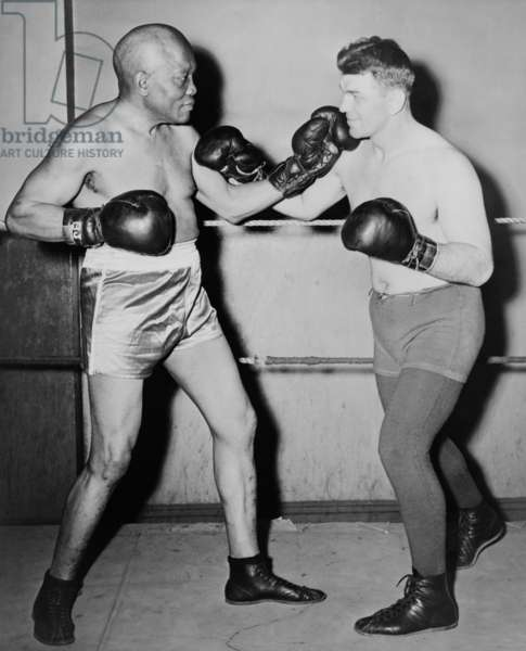 Former heavyweight champion, Jack Johnson, left, in fighting pose with Steve Dudos. 1945. Johnson was then 68 years old and died the following year.