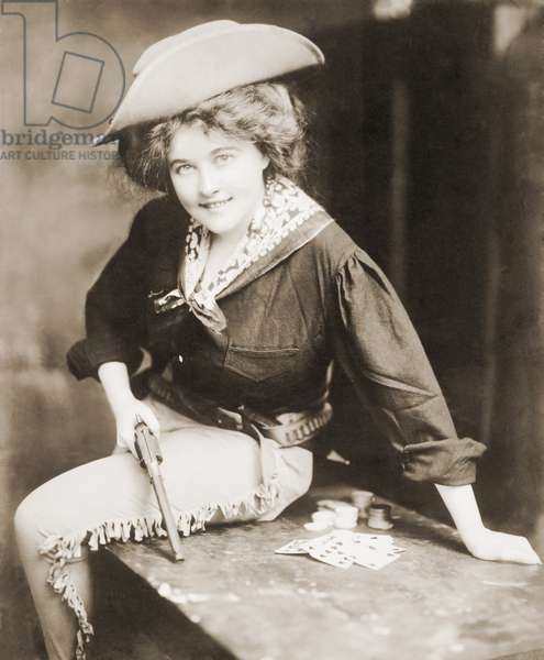 Turn of the century Cowgirl holding revolver, seated on a table, with playing cards and chips. c. 1900
