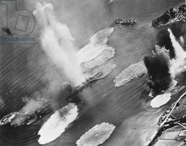 U.S. carrier planes bomb Japanese cruisers anchored in the Kure Harbor Naval Base at Honshu. The warship under attack is almost completely hidden by water geysers from near misses. July 1945. World War 2