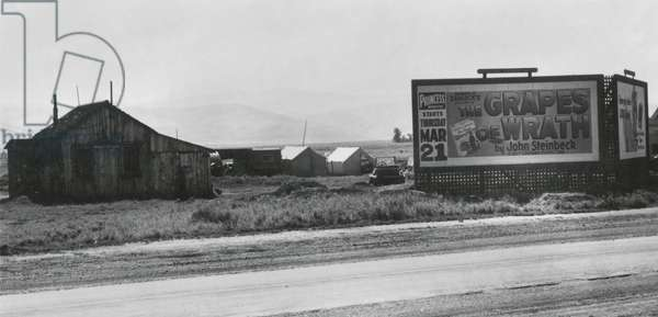Roadside migrant camp behind, 'Grapes of Wrath,' billboard, April 1940 (b/w photo)