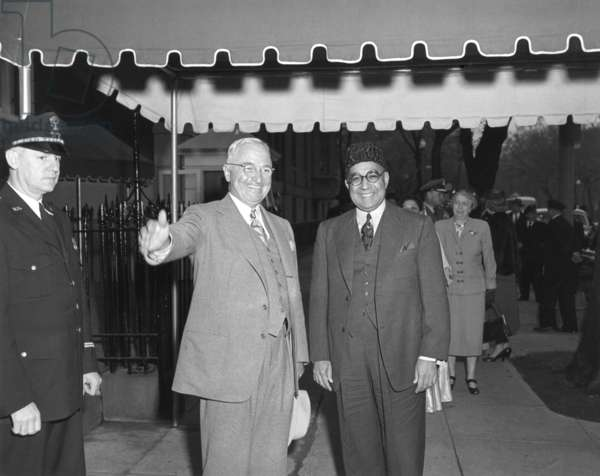 President Harry Truman and Prime Minister Liaquat Ali Khan of Pakistan in Washington, D.C. In background is First Lady Bess Truman. May, 3, 1950.