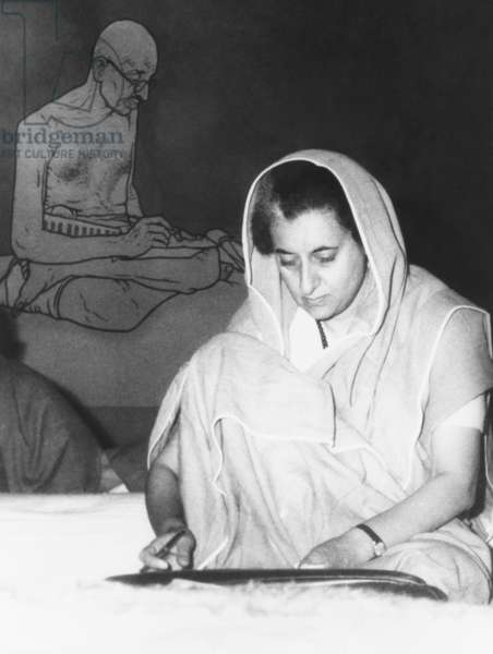 Indian Prime Minister Indira Gandhi during the annual session of the ruling Congress Party. Feb. 2, 1966. Seated on the floor, she meets her fellow countryman in the style of Mahatma Gandhi, pictured behind her