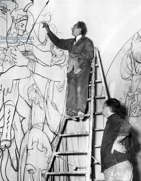 Jean Cocteau works on the mural of the life of St. Peter in St. Peter's Chapel, Villefranche, France. Painter Jean Paul Brusset watches, 1956