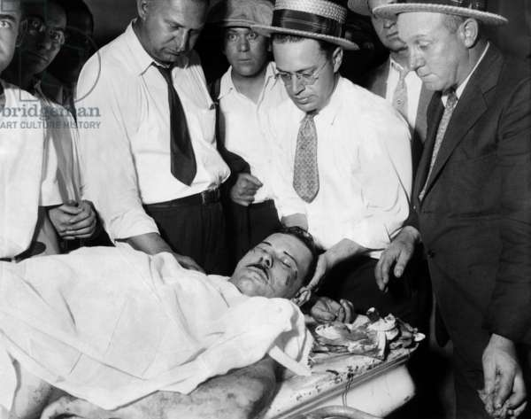 John Dillinger, Public Enemy No.1, lying on a slab in the county morgue in Chicago. Surrounded by policemen and coroner's assistants, he was killed outside a Chicago movie theater by FBI agents and police on July 23, 1934