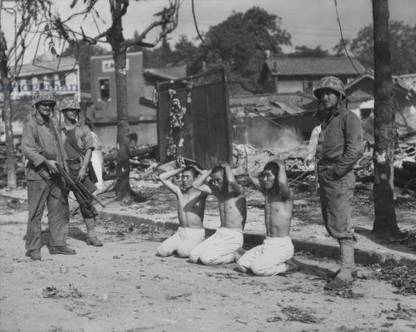 U.S. Marines guarding three captured North Koreans, in an urban setting. c. 1950. Probably near Seoul, Korea. Exact date/location unknown. Korean War, 1950-53