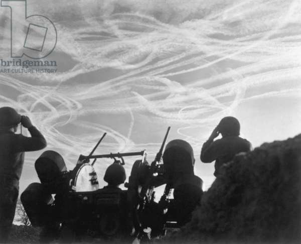 Christmas Day dogfights streaked the sky with vapor trails from Allied and German planes. Soldiers of an anti-aircraft battery watch the action over Puffendorf, Germany. Dec. 25, 1944. Battle of the Bulge, World War 2