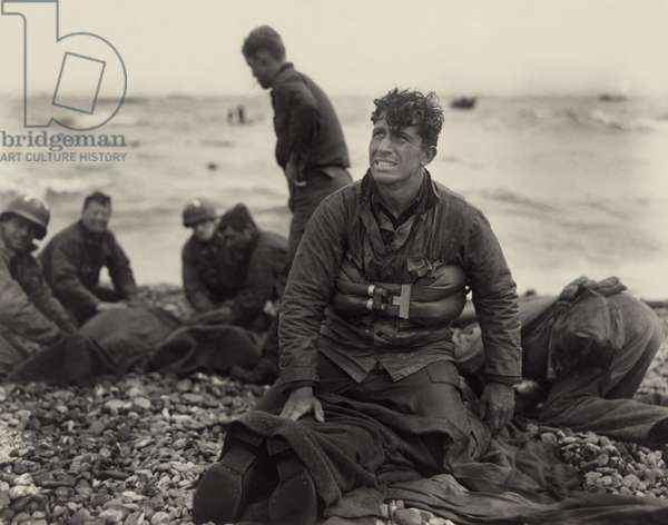 World War II. American soldiers on Omaha Beach recovering the dead after the D-Day invasion of France. June 1944, by U.S. Army Signal Corps photographer, Walter Roseblum
