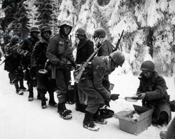 U.S. Infantrymen at field mess on their way to La Roche, Belgium. At this time the Germans were retreating, and Allies were on the offensive. January 13, 1945. Battle of the Bulge, World War 2