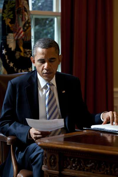President Barack Obama reads a document in the Oval Office, Feb. 21, 2012