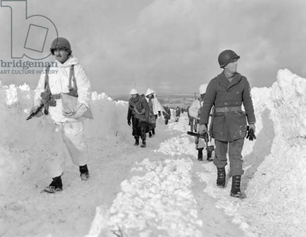 U.S. soldiers patrol on a path plowed through snow in the Ardennes during the Battle of the Bulge. Some infantry men have full white uniforms while others have only partial or no camouflage covering. c. Dec. 26, 1944 through Jan. 25, 1945. World War 2
