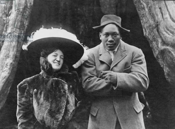 World Heavyweight Champion boxer Jack Johnson (1878-1946) and his white wife, in Vancouver, B.C. in 1909. Johnson is returning from his victory over Tommy Burns in Sydney. Johnson is playfully posed as Napoleon