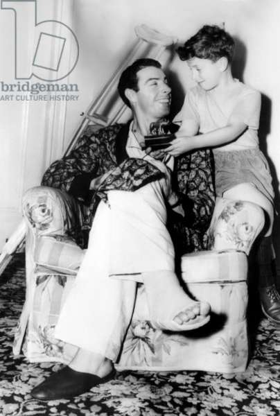 Joe DiMaggio, recovering from an operation on his right heel, shows his son Joe jr. a stauette given to him as a gift by the Rome Athletic Club in Italy. c. December 1948