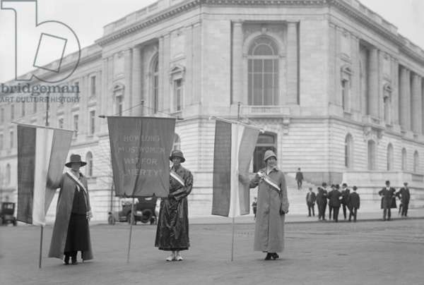 Suffragettes picketing the Senate Office Building in Washington in 1918. Left to right: Mildred Gilbert, Pauline Floyd, Vivian Pierce. They display a banner, 'How Long Must Women Wait for Liberty?'