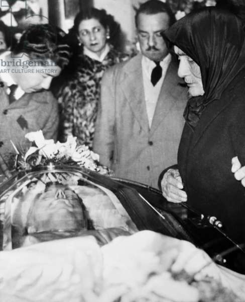 An aged woman, shrouded in mourning, looks into the coffin of Argentina's Eva Peron. At age 105, the woman wanted to pay her respects to the late Mrs. Juan Peron in gratitude for having obtained an old-age pension through her.