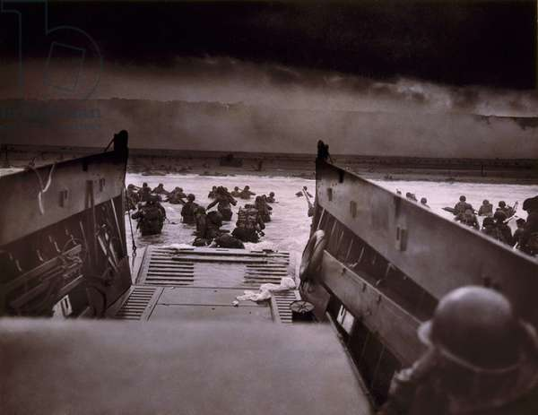 American soldiers wade from Coast Guard landing craft toward the Omaha Beach against machine gun fire on D-Day. June 6, 1944, by Coast Guard photographer, Robert F. Sargent