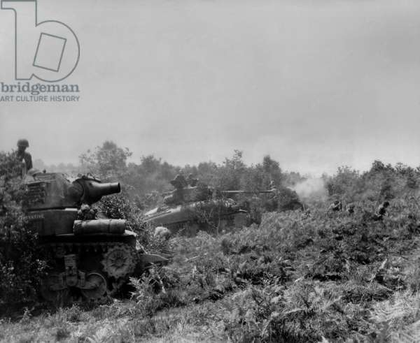 Three U.S tanks firing on German positions in the Battle of the Falaise Pocket. Three soldiers are on the ground in front of the tanks. The Location is near Barenton, Normandy, where the German counter offensive was stopped on August 17, 1944. France, World War 2