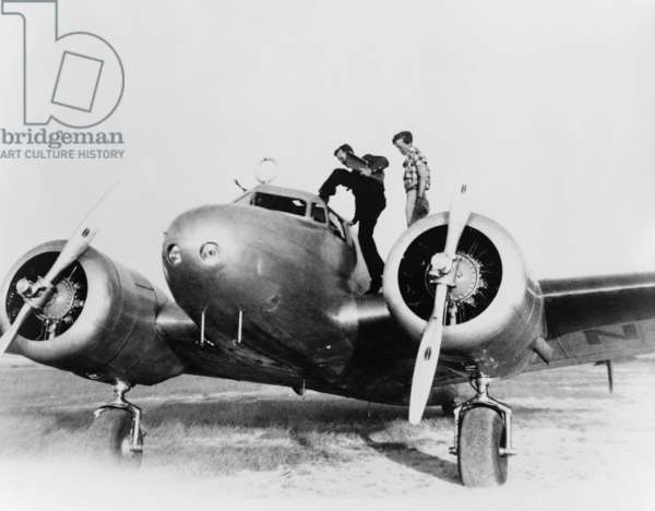 Amelia Earhart stanind on the wing of her Lockheed L-10E Electra airplane. At right is Fred Noonan, her navigator entering the cockpit, during a stop in Puerto Rico during their failed attempt to fly around the world. 1937