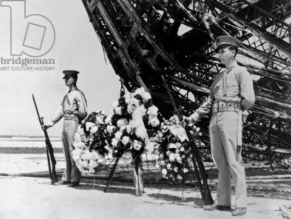 Hindenburg dead are honored on Memorial Day. Two U.S. Marines stand guard at the wreath place at the prow of the ill-fated dirigible. The skeleton of the craft still lies where it fell at Lakehurst, N.J. more than three weeks after it burned on landing. May 31, 1937