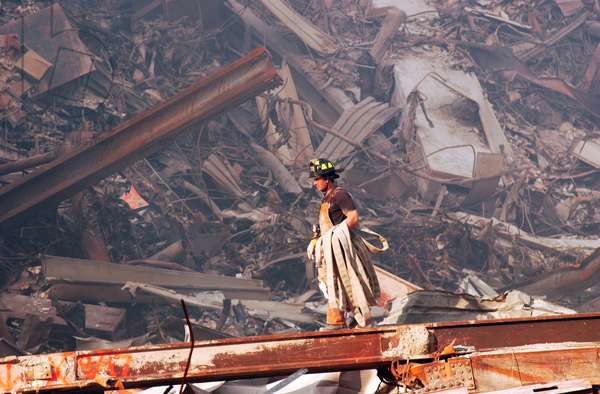 NYC Fire fighter carries a fire hose over smouldering fires and wreckage at Ground Zero, Sept. 18, 2001. World Trade Center, New York City, after September 11, 2001 terrorist attacks