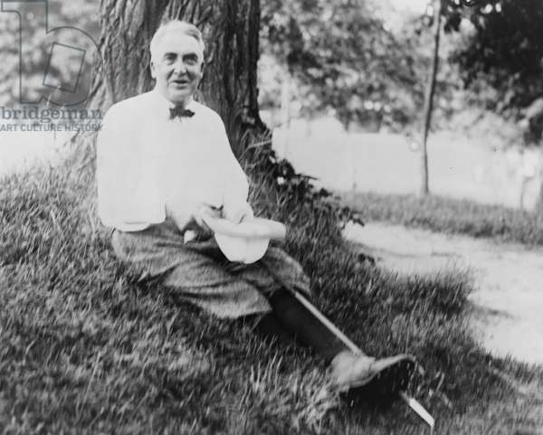 President Warren Harding (1865-1923) wearing golfing clothes, seated on ground beneath tree
