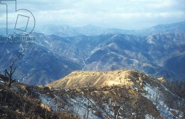 Desolate UN trench line along the mountainous 38th Parallel. Heartbreak Ridge, a fiercely contested position in Sept.-Oct. 1952, is visible in the background. Heartbreak Ridge was one of several battles a few miles north of the 38th parallel in North Korea. Korean War, 1950-53