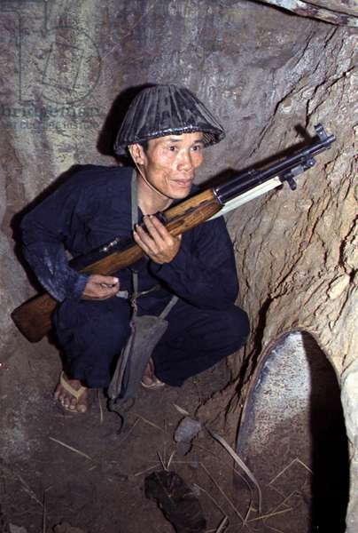 Vietnam War, a Viet Cong, soldier crouches in a bunker with an SKS rifle, c.late 1960s
