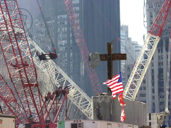 At the World Trade Center disaster site workers use heavy machinery to remove one of the steel beams from the section dubbed 'God's House' in reference to the many crosses inside, Oct. 10 2001