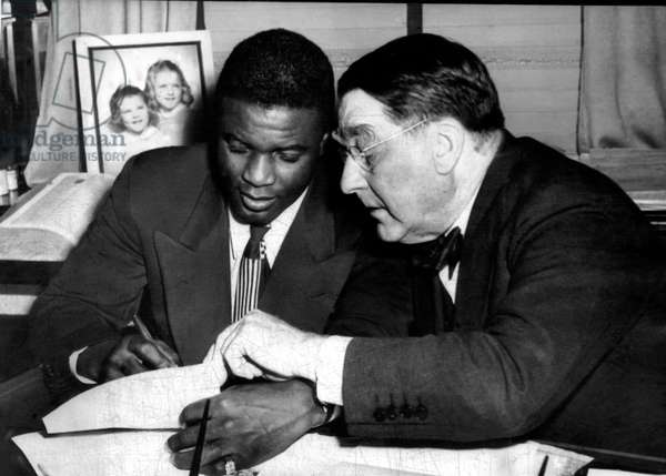 Jackie Robinson (left), being signed by Branch Rickey (right), to a one year contract to play for the Brooklyn Dodgers, 1945.