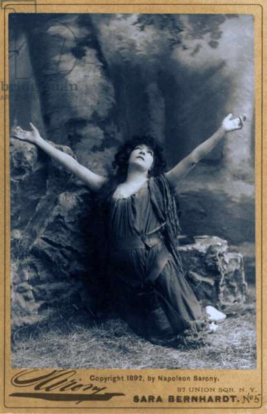 Sarah Bernhardt (1844-1923), French actress, in dramatic pose, kneeling with arms raised. c. 1892