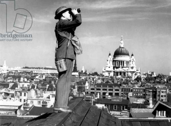 Aircraft spotter searches the sky with binoculars during the Battle of Britain. St. Paul's Cathedral is in the background. World War 2, c. 1940-41
