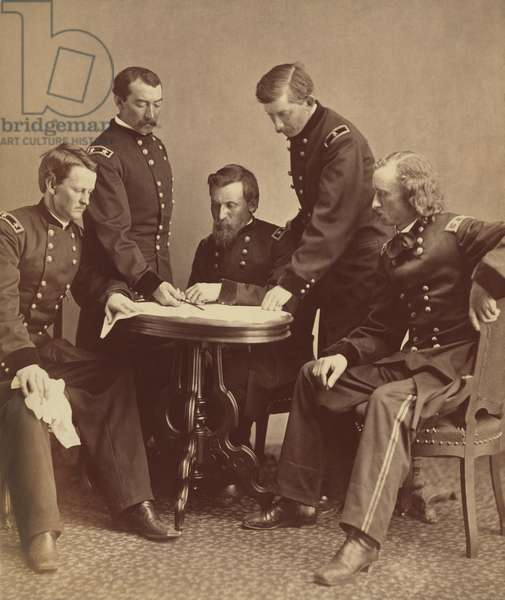 Major General Philip Sheridan with his generals examining a document at a table. L to R: Generals Wesley Merritt, Philip Sheridan, George Crook, James William Forsyth, and George Armstrong Custer, examining a document at a table. All five men would fight in the Indian Wars. Photo taken by Alexander Gardner, Jan. 2, 1865