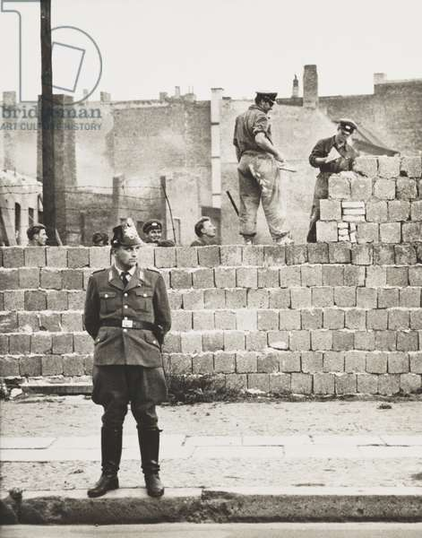 West Berlin policeman stands before the concrete block wall dividing East and West Berlin. Along Bernauer Strasse, East Berlin workmen add blocks to increase height of the barrier. Oct. 11, 1961