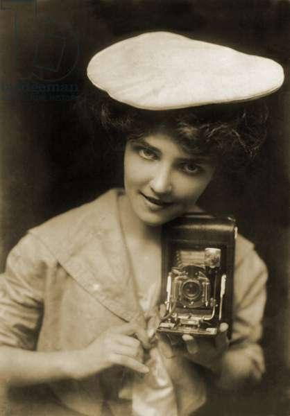 THE KODAK GIRL, a pretty girl posed with camera in a 1909 Kodak advertisement