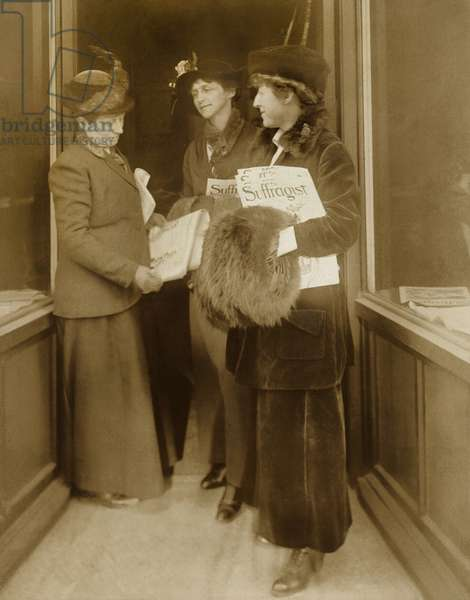 Jeanette Rankin, with hat, fur muff, and several issues of THE SUFFRAGIST, the magazine of the militant National Women's Party with two women, who also hold copies of the paper. Rankin was later serve two terms in Congress representing Montana