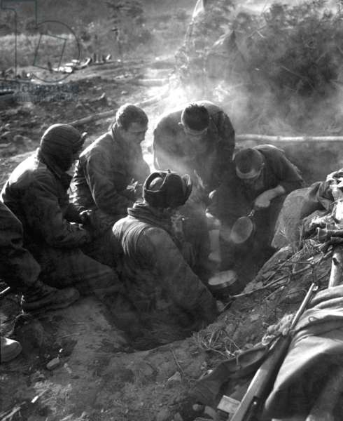 U.S. Soldiers a 7th Infantry Regiment go native, cooking rice in their foxhole in the Kagae-dong area, North Korea. Dec. 7, 1950. Korean War, 1950-53