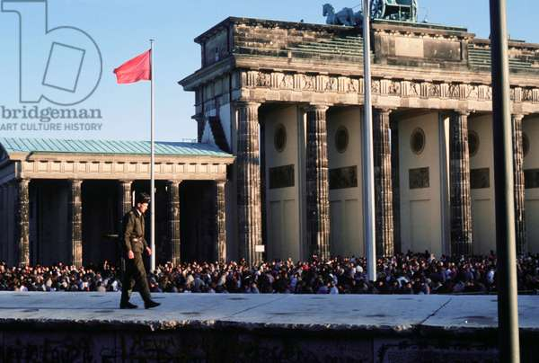 Crowds of Berliners around the Brandenburg Gate following the structure's official opening on Dec. 22 1989. In the foreground an East German guard walks on the Berlin Wall