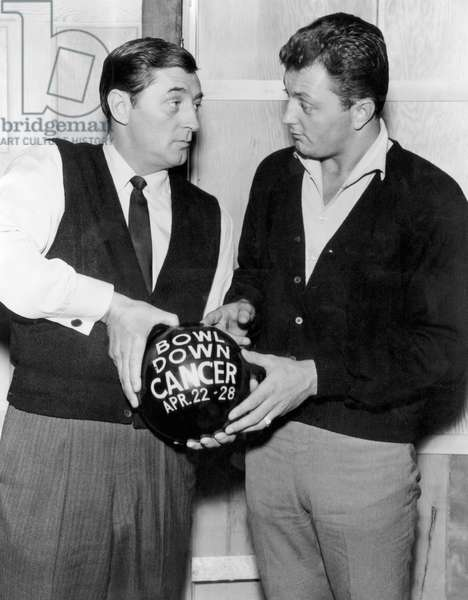 American actor Robert Mitchum and his son, Jim Mitchum, discussing 'Bowl Down Cancer Week', a week long bowling and cancer educational campaign, 1962.