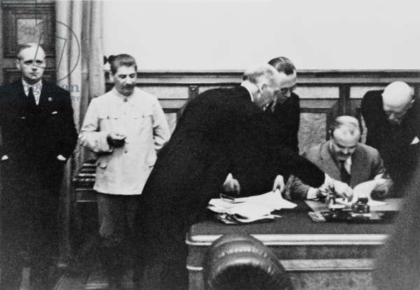 Soviet Foreign Minister Molotov signs the Nazi-Soviet Nonaggression Pact in the Kremlin on August 23, 1939. Left to right: Von Ribbentrop, Stalin, Gauss, Hilger, Molotov, von der Schulenburg