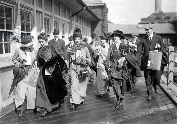 Mrs. Emmeline Pankhurst, the English militant leader (center), is shown leaving Ellis Island today with party of suffragists after President Wilson had ordered her release. October 20, 1913.