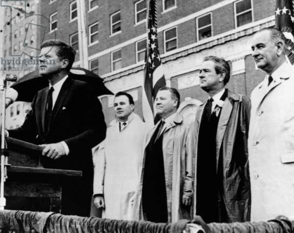 Morning of the day of JKF's assassination. President Kennedy speaks to a crowd in front of the Texas Hotel in Fort Worth during a light rain. Behind him are (L-R): Senator Ralph Yarborough; Texas Governor John Connally, and Vice President Lyndon Johnson. Nov. 22, 1963