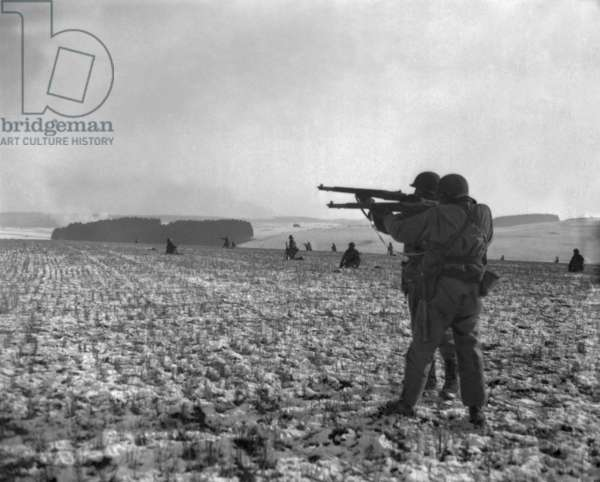 U.S. soldiers fire at Germans positions to relieve besieged airborne troops in Bastogne, Belgium. Dec. 27, 1944. Battle of the Bulge, World War 2