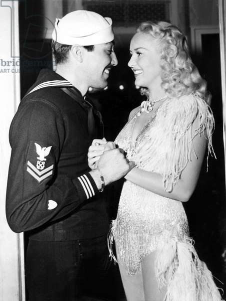 Betty Grable is visited at 20th Century Fox by Cesar Romero, who is visitng his home studio after eight months duty in the Central Pacific. Hollywood, CA, 9/1/44