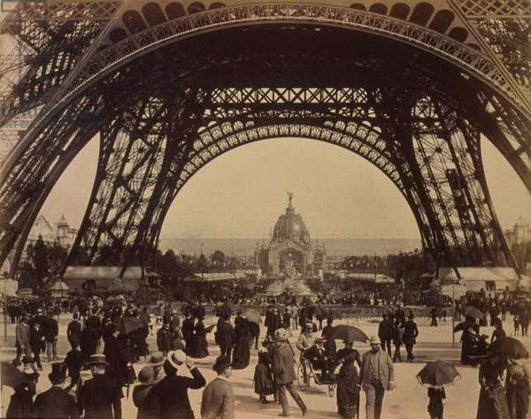Eiffel Tower, view toward the Central Dome, Paris Exposition, with a crowd of people walking under its arched base. 1889