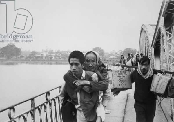 Refugees flee Tet Offensive in Hue. Refugees flee Hue by crossing the Perfume River before the Bridge was destroyed by communist troops. During occupation and fighting in Hue, 5000 civilians were killed. c. January 31, 1968