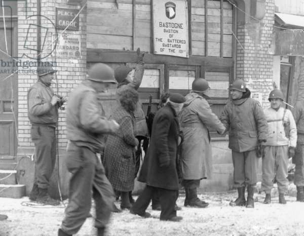 U.S. military personnel revisiting Bastogne, Belgium, six years after the Battle of the Bulge. The group meets beneath a sign reading, 'Bastogne Bastion of the Battered Bastards of the 101st'. Dec. 1950. World War 2