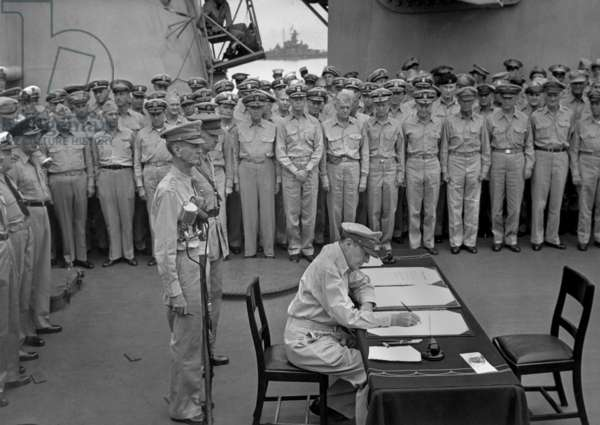 Douglas MacArthur signs documents during Japanese surrender ceremonies on the USS MISSOURI in Tokyo Bay. Standing behind MacArthur are Gen. Jonathan Wainwright and British Gen. Arthur Percival. Japan, Sept. 2, 1945