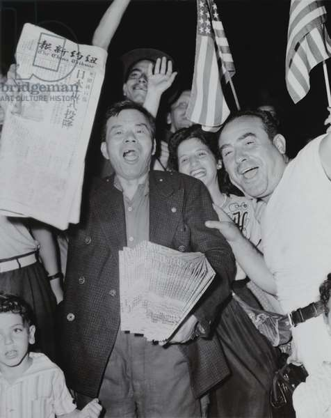 Chinese newspaper vendor, among crowd waving American flags in Chinatown, New York, on V-J Day. 'The China Tribune', announces surrender of the Japanese ending World War 2. Aug. 15, 1945. World War 2