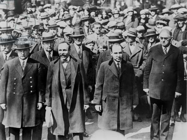 Bartolomeo Vanzetti (left) and Nicola Sacco, manacled together before they received death sentences for payroll guard murder they were convicted of seven years earlier. They are surrounded by heavy guard and onlookers, as they enter the courthouse at Dedham, Massachusetts